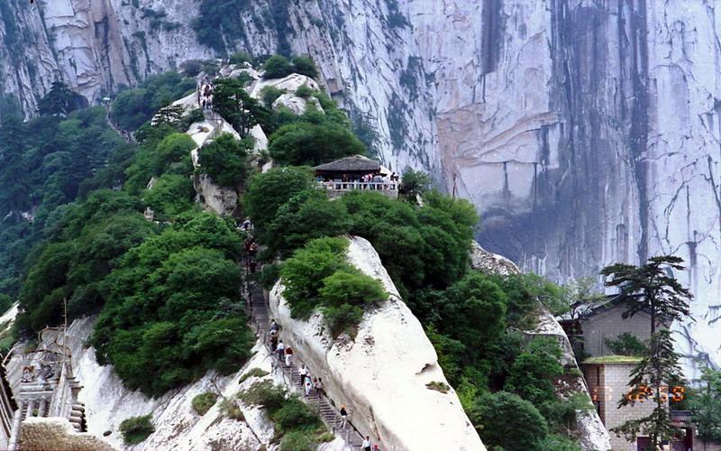 华山位于华阴县境内,距西安 120 公里,为五岳中的西岳。华山之险居五岳之首,华山自古一条道,素有奇险天下第一山之称。   华山有东、西、南、北、中五峰。东峰是华山的奇峰之一,因峰顶有朝台可以观看日出、美景,故又名朝阳峰。北峰也叫云台峰,山势峥嵘,三面绝壁,只有一条山道通往南面山岭,电影 《智取华山》即取材于此西峰叫莲花峰, 峰顶有一块斧劈石,相传神话传说故事《宝莲灯》中的沉香劈山救母就发生在这里。南峰即落雁峰,是华山主峰,海拔2083米,也是华山最险峰,峰上苍松翠柏,林木葱郁,峰东有凌空飞架的
